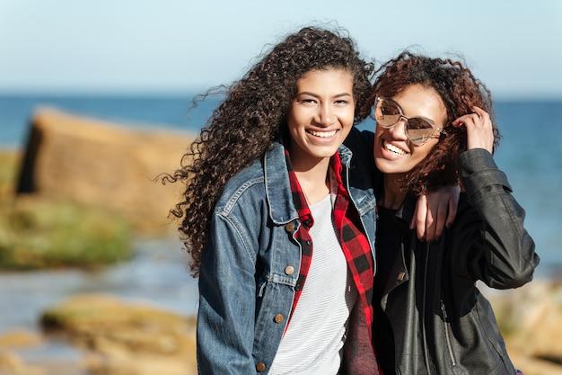 Sonrientes amigos de la mujer africana caminando al aire libre en la playa.