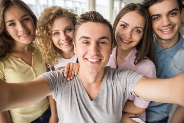 Sonrientes amigos tomando selfie con teléfono en la universidad.