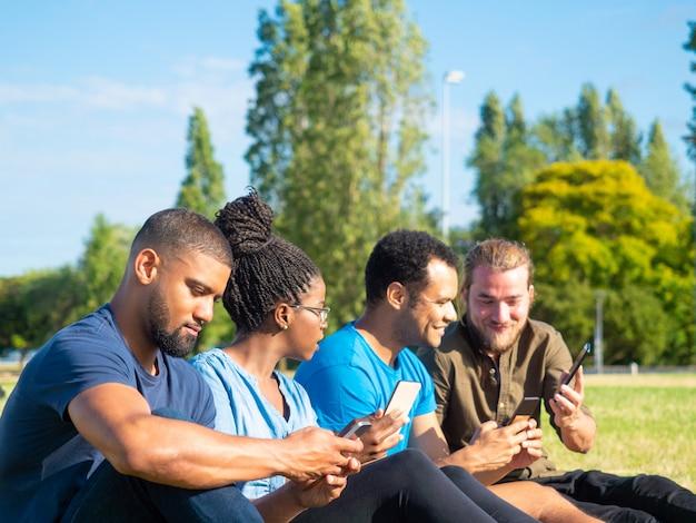 Sonrientes amigos usando teléfonos inteligentes en el parque
