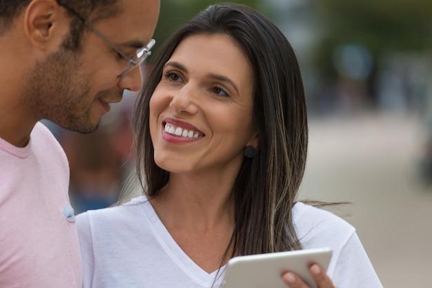 Sonrientes buenos amigos con tableta en la calle