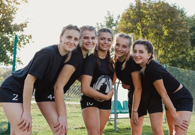 Sonrientes chicas deportivas mirando al fotógrafo