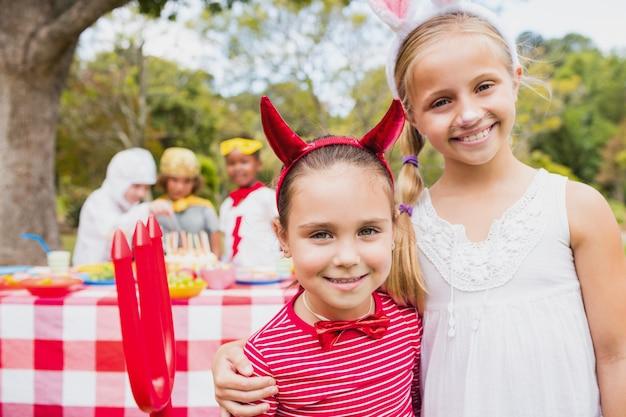 Sonrientes chicas vistiendo trajes durante una fiesta de cumpleaños