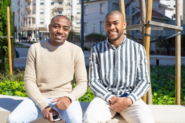 Sonrientes chicos afroamericanos sentados en el banco con teléfonos