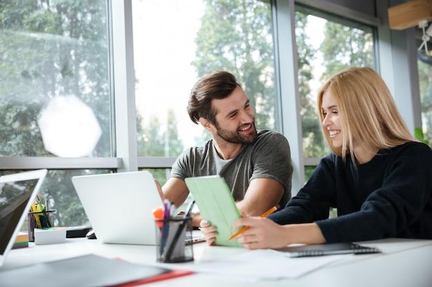 Sonrientes colegas jóvenes sentados en coworking de oficina