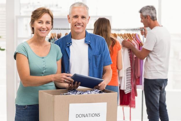 Sonrientes colegas de negocios ocasionales con caja de donación