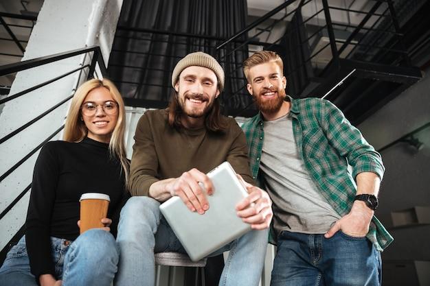 Sonrientes colegas en la oficina con tableta