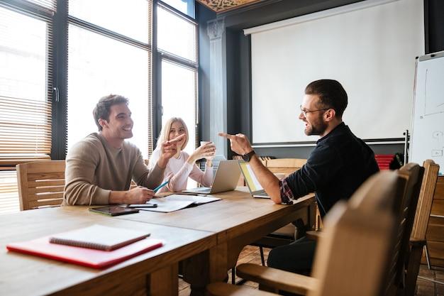 Sonrientes colegas sentados cerca del café mientras trabajan con computadoras portátiles