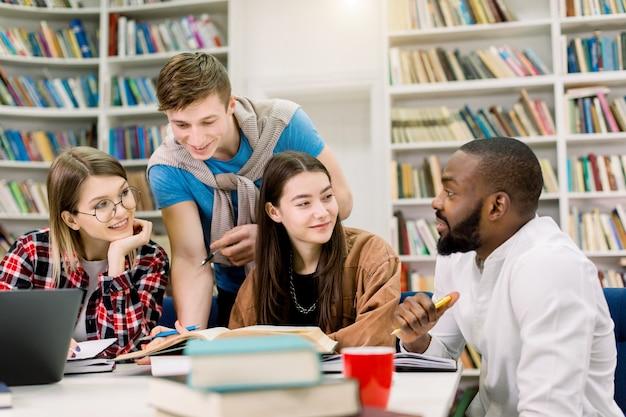 Sonrientes estudiantes multirraciales alegres sentados en la biblioteca y leyendo libros durante su preparación para los exámenes o la clase práctica, comparten información y se comunican entre sí.