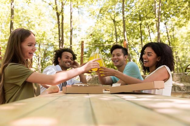 Sonrientes jóvenes amigos amigos multiétnicos al aire libre bebiendo jugo comiendo pizza.