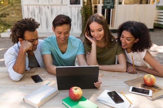 Sonrientes jóvenes amigos amigos multiétnicos al aire libre usando tableta