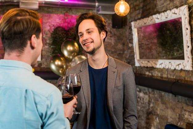 Sonrientes jóvenes amigos celebrando y brindando vino en el bar