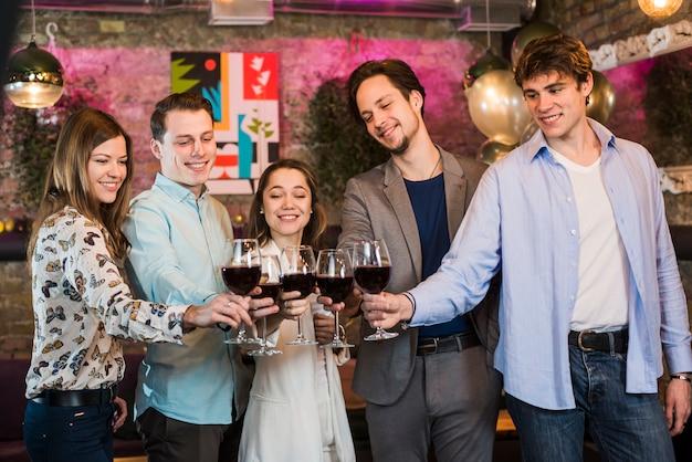 Sonrientes jóvenes amigos disfrutando de una fiesta brindando vino en el club
