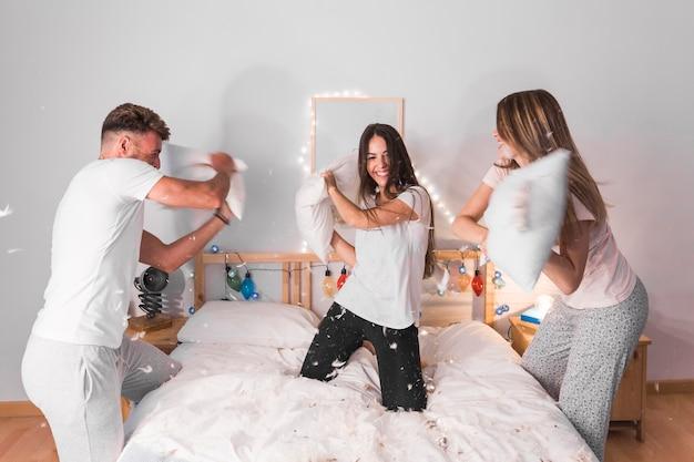 Sonrientes jóvenes amigos disfrutando luchando con almohada en el dormitorio