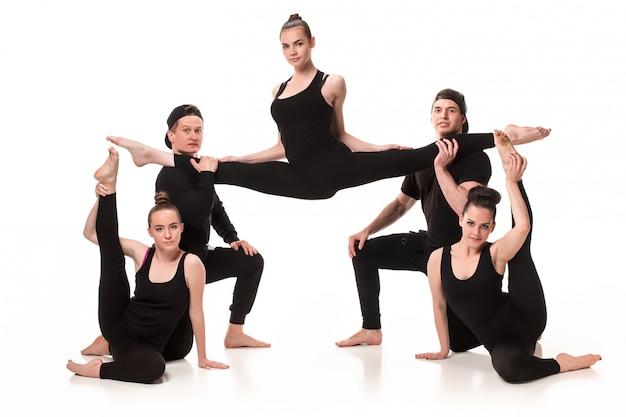 Sonrientes jóvenes en forma haciendo ejercicio y estiramientos
