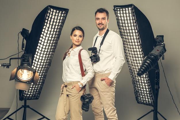Sonrientes jóvenes fotógrafos profesionales posando en el estudio