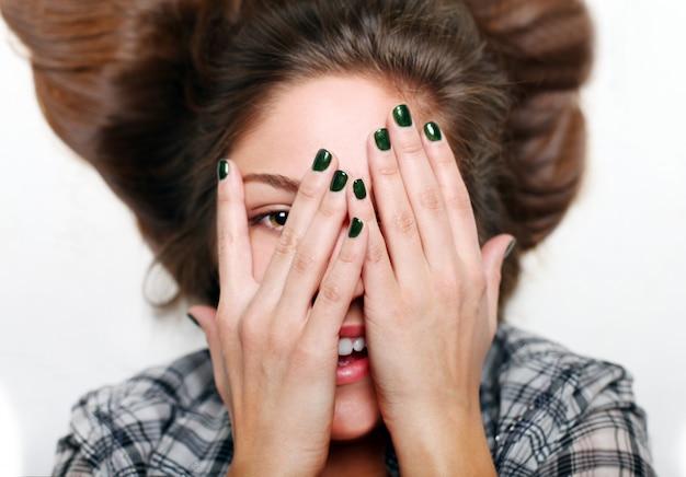 Sonrientes manos adolescentes de cara, arte de uñas verde