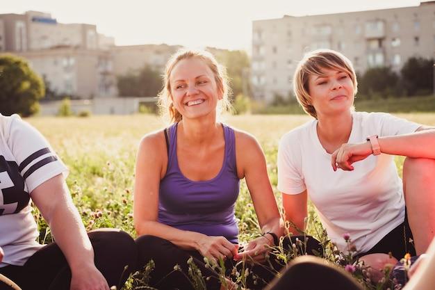 Sonrientes mujeres jóvenes sentadas conversando con amigos