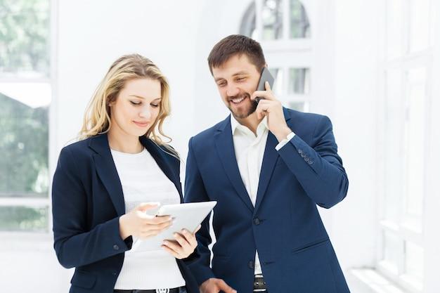 Los sonrientes trabajadores de oficina masculinos y femeninos con computadora portátil y teléfono