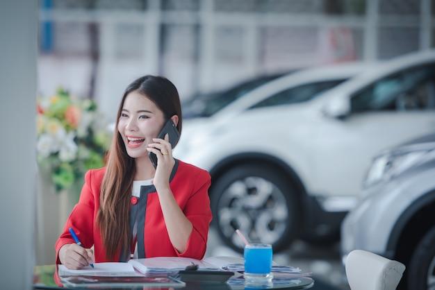 Sonrientes vendedores asiáticos haciendo una llamada telefónica en el nuevo showroom de automóviles