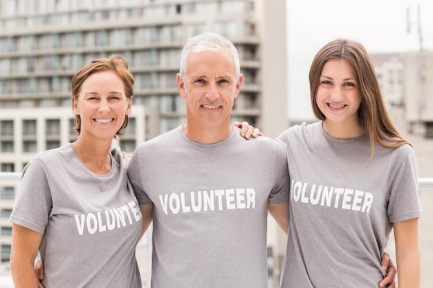 Sonrientes voluntarios abrazándose unos a otros