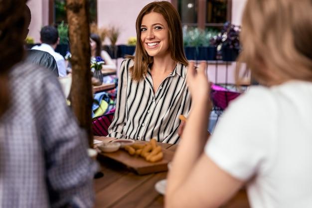 Sonrió atractiva hermosa mujer caucásica con amigos en el acogedor café