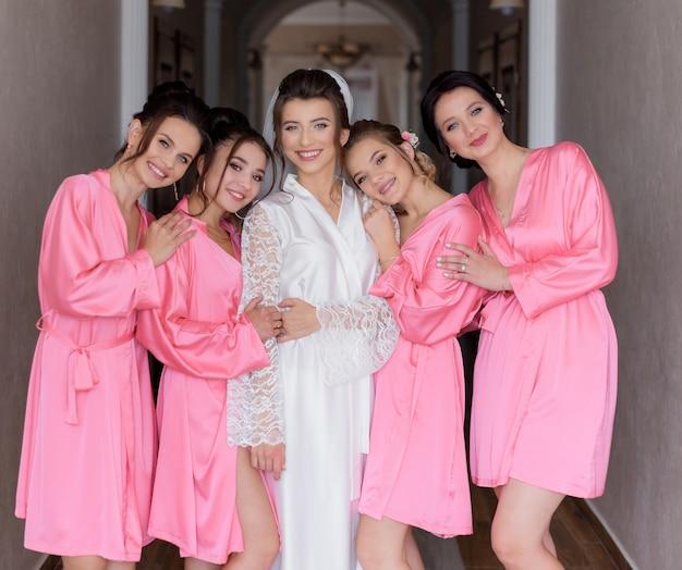 Sonrió felices damas de honor vestidas con ropa de dormir de seda rosa con hermosa novia en el pasillo
