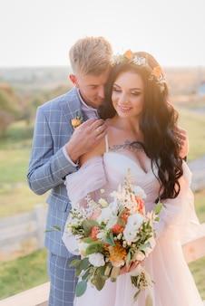 Sonrió tierna pareja de novios enamorados al aire libre en el prado con hermoso ramo de novia y corona en el día soleado
