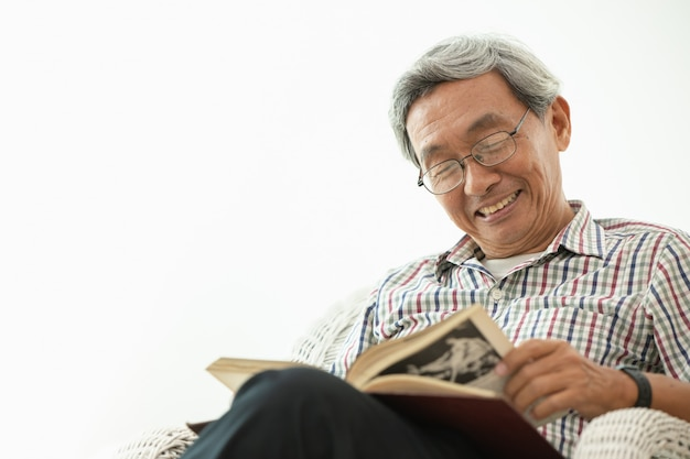 Sonrisa de ancianos asiáticos mientras está sentado leyendo en sala blanca
