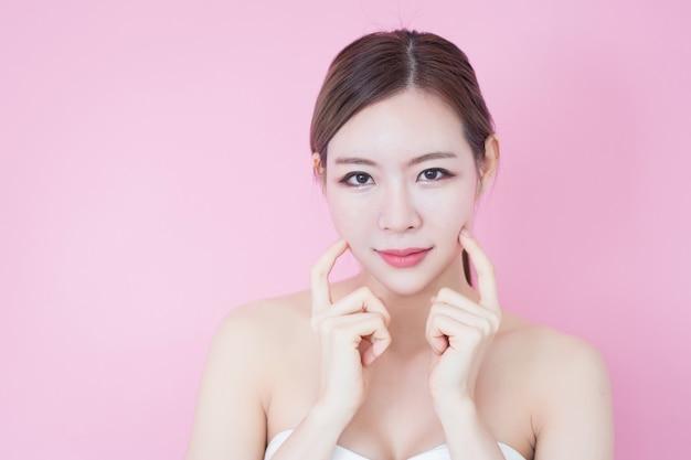 Sonrisa asiática caucásica joven hermosa de la mujer con maquillaje natural de la cara fresca limpia de la piel. cosmetología, cuidado de la piel, limpieza facial