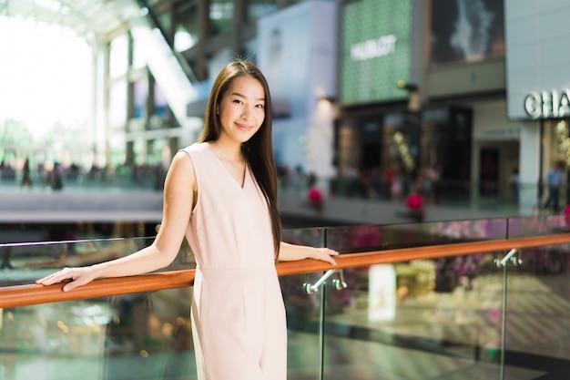 Sonrisa asiática hermosa de la mujer y feliz en alameda de compras