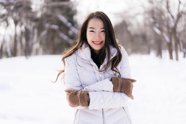Sonrisa asiática joven hermosa de la mujer feliz para el viaje en la estación del invierno de la nieve