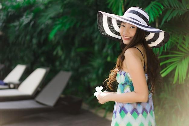 Sonrisa asiática joven hermosa de la mujer del retrato y feliz alrededor del jardín al aire libre