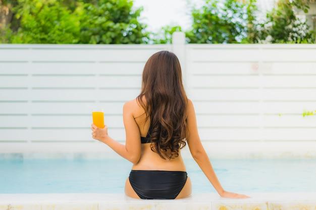 La sonrisa asiática joven hermosa de la mujer del retrato feliz se relaja alrededor de piscina en el centro turístico del hotel para el ocio