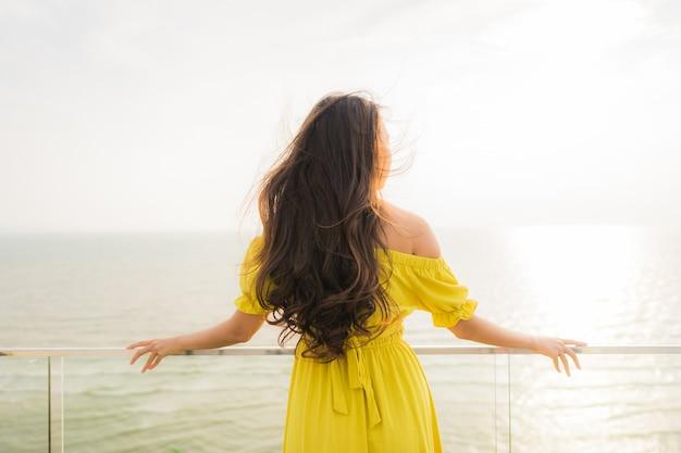 La sonrisa asiática joven hermosa de la mujer del retrato feliz y se relaja en el balcón al aire libre con la playa y el oce del mar