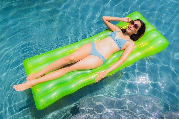 La sonrisa asiática joven hermosa de la mujer del retrato feliz se relaja y el ocio en la piscina