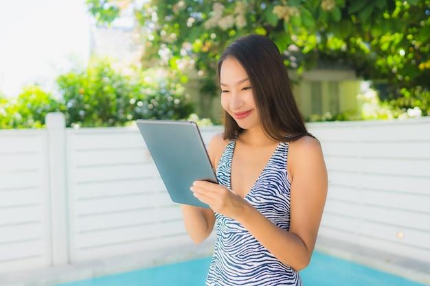 La sonrisa asiática joven hermosa de la mujer del retrato feliz se relaja con la tableta alrededor de la piscina i