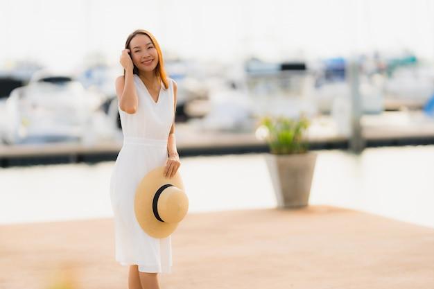 La sonrisa asiática joven hermosa del ocio de la mujer del retrato feliz se relaja alrededor de puerto del yate