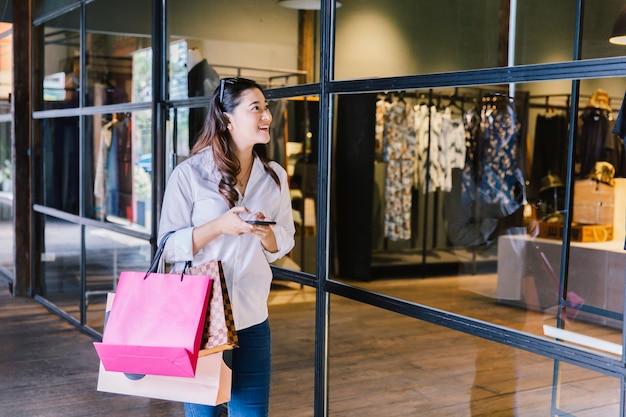 La sonrisa asiática de la mujer con los panieres goza en alameda de compras