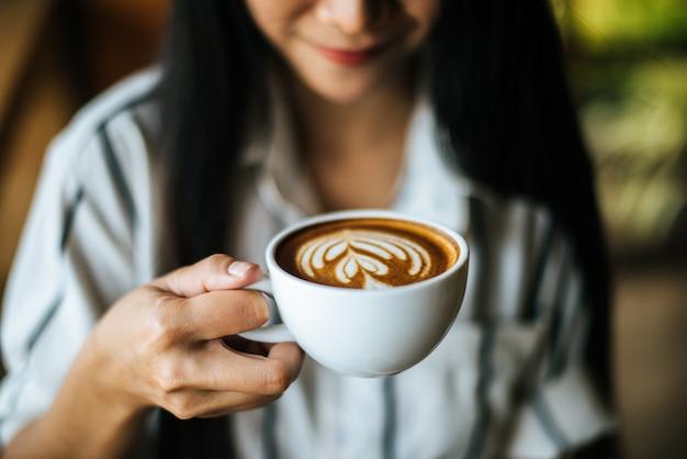 La sonrisa asiática de la mujer del retrato se relaja en café de la cafetería