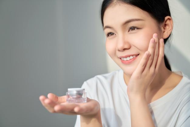 Sonrisa belleza de piel de mujer asiática y mano sosteniendo una botella de crema de producto para productos de spa y maquillaje. la piel es suave y hermosa.