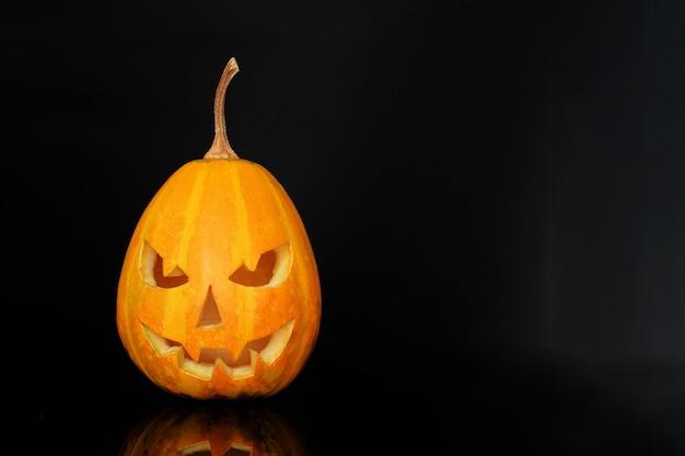 Sonrisa de calabaza de halloween y ojos rasposos para la noche de fiesta. vista cercana de la aterradora calabaza de halloween en fondo negro.