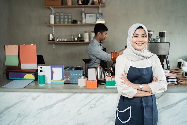 Sonrisa de camarera femenina con las manos cruzadas