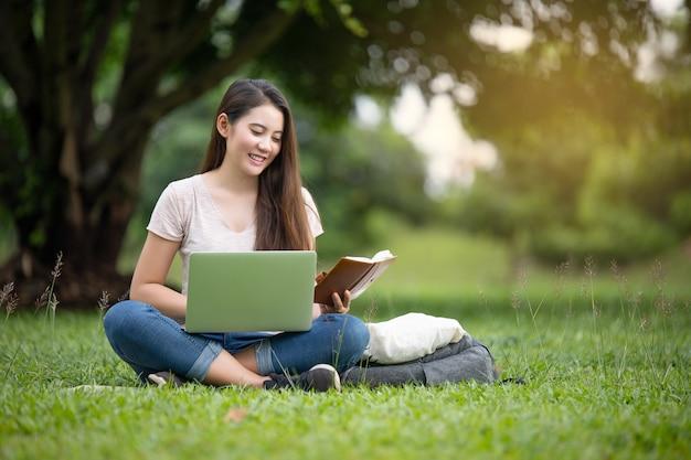 Sonrisa confiada mujer bastante joven que se sienta en lugar de trabajo en al aire libre con la computadora portátil. concepto de trabajo