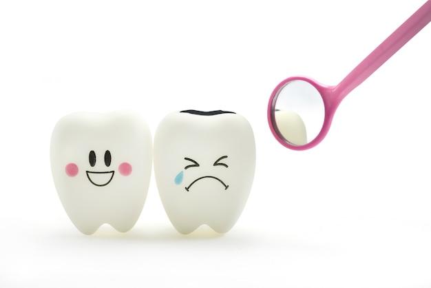 Sonrisa del diente y emoción del grito con el espejo dental en el fondo blanco.