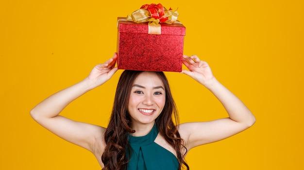 Sonrisa feliz cara linda chica asiática con cabello oscuro con caja de regalo sobre la cabeza con encantador y emocionado, foto de estudio sobre fondo amarillo. celebrar y concepto de fiesta.