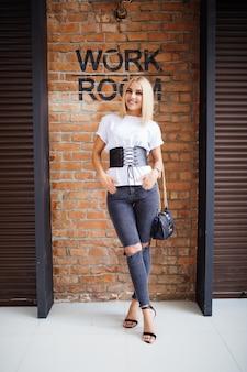 Sonrisa feliz chica rubia cerca de la pared de ladrillos viejos