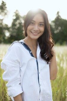 Sonrisa feliz de las mujeres asiáticas en tiempo de relajación en el prado y la hierba
