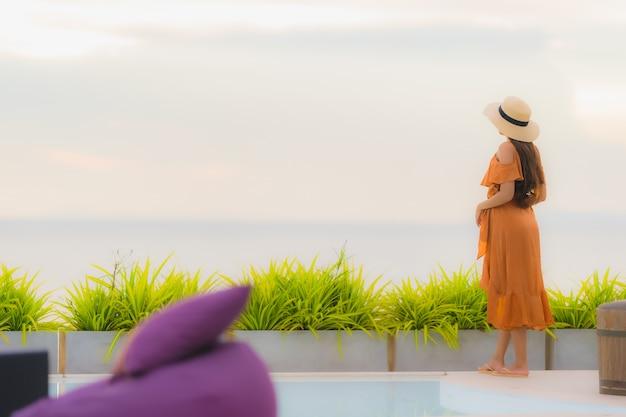 Sonrisa feliz de la forma de vida asiática joven hermosa de la mujer del retrato con ocio casi océano de la playa del mar