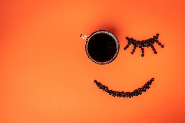 Sonrisa feliz de granos de café y taza de café sobre fondo naranja. buenos días y despierta el concepto.