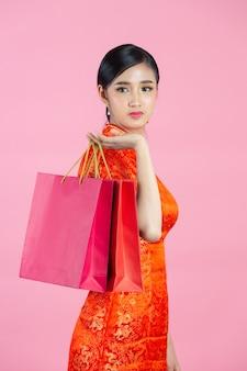 Sonrisa feliz hermosa mujer asiática y compras en año nuevo chino sobre fondo rosa.